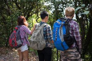 close-up van wandelaarvrienden die van achteren met rugzakken in bos staan
