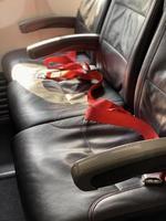lege vliegtuigstoel met rode veiligheidsgordels foto