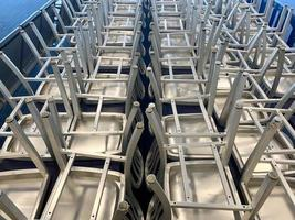 opgestapelde metalen stoelen in rijen