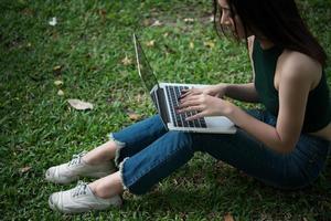jonge mooie vrouw zittend op het groene gras en met behulp van laptop in het park