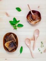 honingraat in houten kom met kruiden foto