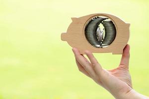 hand met houten spaarvarken met stapels munten binnen op groene achtergrond foto