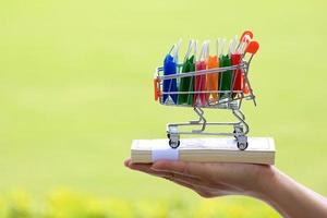 handen met miniatuur winkelwagentje gevuld met kleurrijke boodschappentassen in zonlicht op groene achtergrond foto