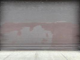 een metalen garagedeur met roestvlekken op een betonnen stoep