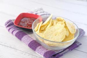 kom met smakelijke chips op houten achtergrond