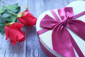 hartvorm geschenkdoos en roze bloem op houten achtergrond