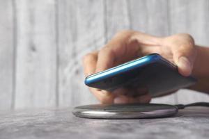 hand opladen van een smartphone met behulp van draadloos oplaadstation, bovenaanzicht