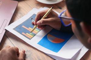 achteraanzicht van jonge man analyseren staafdiagram op papier