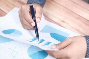 iemands hand met pen analyseren staafdiagram op papier