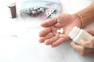 hand van een oudere vrouw met medicijn dat uit de container is gemorst foto