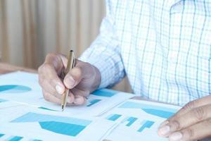 man's hand met een pen analyseren van financiële gegevens en grafiek