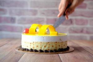 close-up van een vrouwenhand die een zoete desserttaart snijden