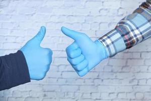 close-up van twee mensen die medische handschoenen dragen die een duim omhoog ondertekenen