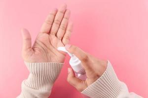 jonge vrouw met behulp van handdesinfecterend middel op roze achtergrond, bovenaanzicht
