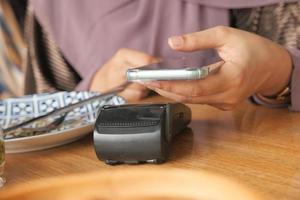 jonge vrouw met behulp van contactloze betaling met smartphone