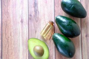 bovenaanzicht van olie en een plakje avocado op houten tafel