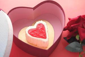 bovenaanzicht van hartvorm cake, geschenkdoos en roze bloem op rode achtergrond