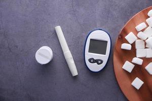 diabetische meetinstrumenten en suikerklontje op zwarte achtergrond