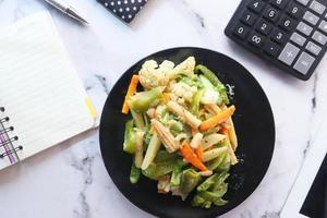 gezond eten concept van vers gekookte groenten op plaat op kantoor tafel foto