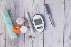bovenaanzicht van diabetische meetinstrumenten en pillen op kleur achtergrond
