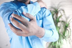 man met pijn in de elleboog, pijnbestrijding concept