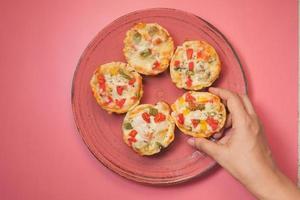 bovenaanzicht van iemands hand het plukken van een stuk pizza van een bord