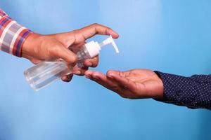 de hand van een persoon die ontsmettingsvloeistof aan een andere persoon geeft foto