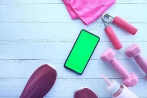 slimme telefoon met sportartikelen op houten vloer