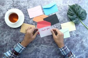 bovenaanzicht van man hand lezen van een bedankbrief foto