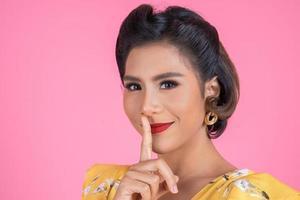 Aziatische vrouw met rode lippen en vinger die stilte tonen foto