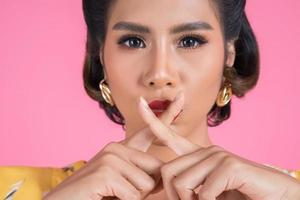 Aziatische vrouw met rode lippen en vinger die stilte tonen