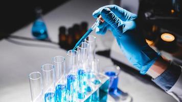 hand in blauwe handschoen gebruikend druppelaar om blauwe vloeistof in flesjes te doen