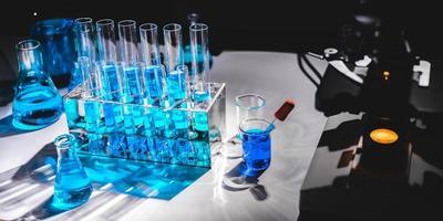flesjes en kolven met blauwe vloeistof naast wetenschappelijke apparatuur