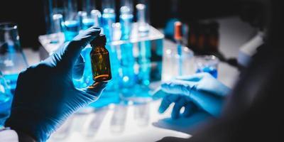 hand in blauwe handschoen met flesje met flesjes blauwe vloeistof op de achtergrond