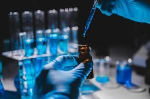 handen in blauwe handschoenen met behulp van druppelaar om blauwe vloeistof in een flesje met flesjes blauwe vloeistof op de achtergrond te doen