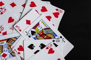 gemengde speelkaarten op een zwarte tafel