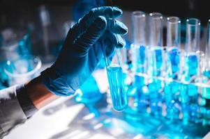 hand in blauwe handschoen met flesje blauwe vloeistof met flesjes blauwe vloeistof op de achtergrond