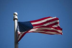 Amerikaanse vlag zwaaien in de blauwe lucht foto