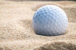 close-up van een golfbal in zand foto