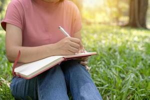 persoon die buiten in een dagboek schrijft foto