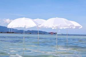 witte paraplu in de oceaan