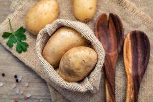 aardappelen in zak met houten keukengerei foto
