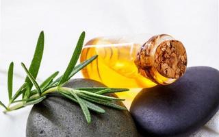 oliefles met rozemarijn en rotsen foto