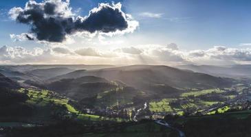 luchtfoto van bomen en heuvels met lage zon in bewolkte blauwe hemel