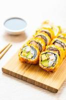 california maki rolt sushi met saus en eetstokjes foto