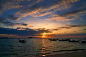 aftekenen boten met kleurrijke bewolkte zonsopgang foto
