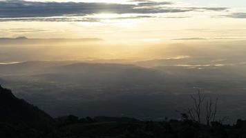 landschap van vallei en bergen met laagstaande zon in een bewolkte hemel