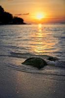 bemoste rots op strand met kleurrijke bewolkte zonsondergang