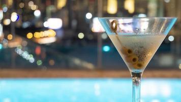 cocktaildrank in martiniglas met vage stadsachtergrond