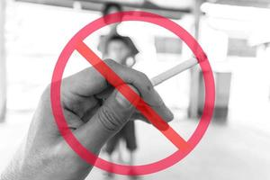 algemeen verbodsteken bovenop de sigaret van de handholding met vage kinderen op achtergrond